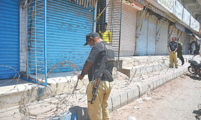 POLICEMEN lay a barbed-wire fence besides the shutters of shops in the Shoe Market at Naya Pull in Hyderabad on Tuesday to foil traders' attempts to open their businesses in violation of the prescribed lockdown.—INP