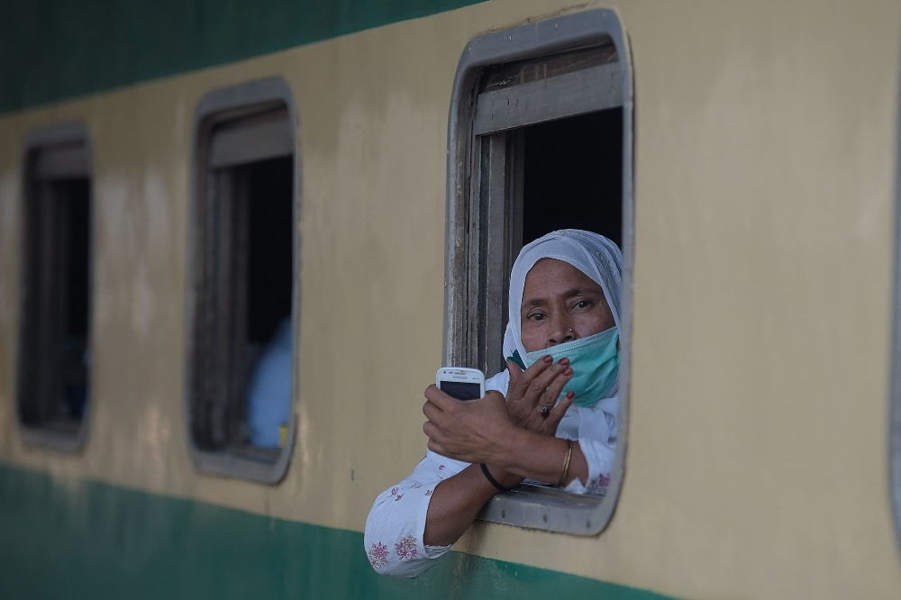 A passenger wearing a facemask looks out from a window of a train in Rawalpindi on May 11. — AFP