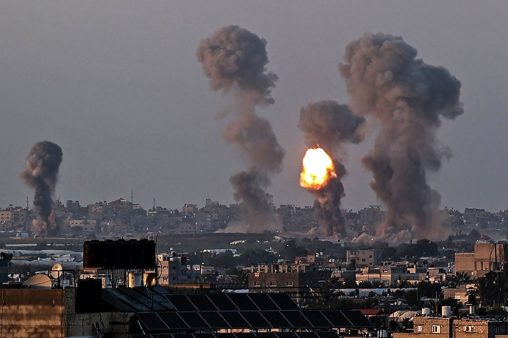 Smoke and a ball of fire rise above buildings in Khan Yunis in the southern Gaza Strip, during an Israeli air strike, on May 12. — AFP