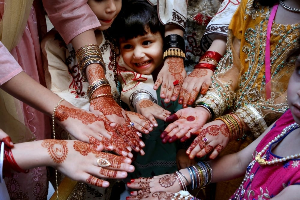 Girls display their hands painted with traditional henna to celebrate Eidul Fitr in Peshawar on May 13. — AP