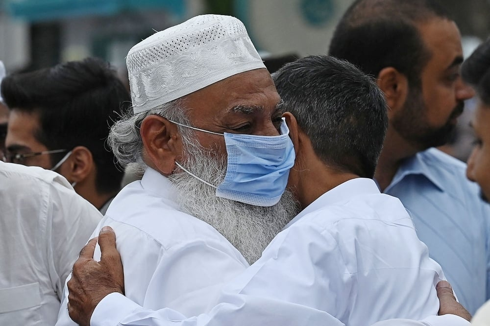 Two men greet each other  after offering Eid prayers in Rawalpindi on May 13. — AFP