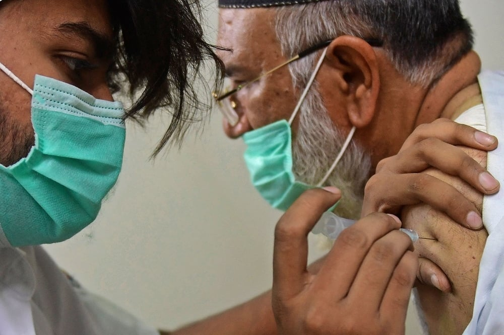 A health worker inoculates a man with the dose of Covid-19 coronavirus vaccine at a vaccination centre in Karachi on May 12. — AFP