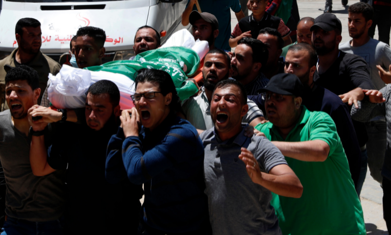 Mourners chant slogans while carrying the body of Awad Abu Selmiya, during a funeral of thirteen Hamas militants outside a mosque in Gaza City on Wednesday. — AP