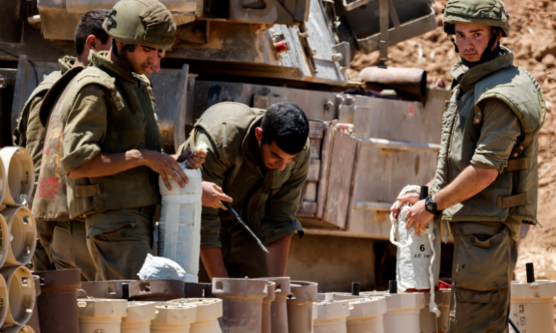Israeli soldiers check artillery shells in an area near the border with Gaza, in southern Israel on Thursday. — Reuters