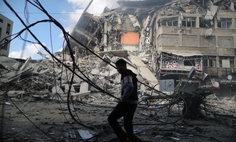 A Palestinian man walks past the remains of a tower building that was destroyed in Israeli air strikes on Thursday. — Reuters