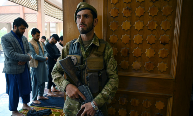 An Afghan security personnel stands guard as Muslims offer prayers to start Eidul Fitr during a three-day ceasefire agreed by the warring Taliban and Afghan forces, at the Abdul Rahman Mosque in Kabul on Thursday. — AFP