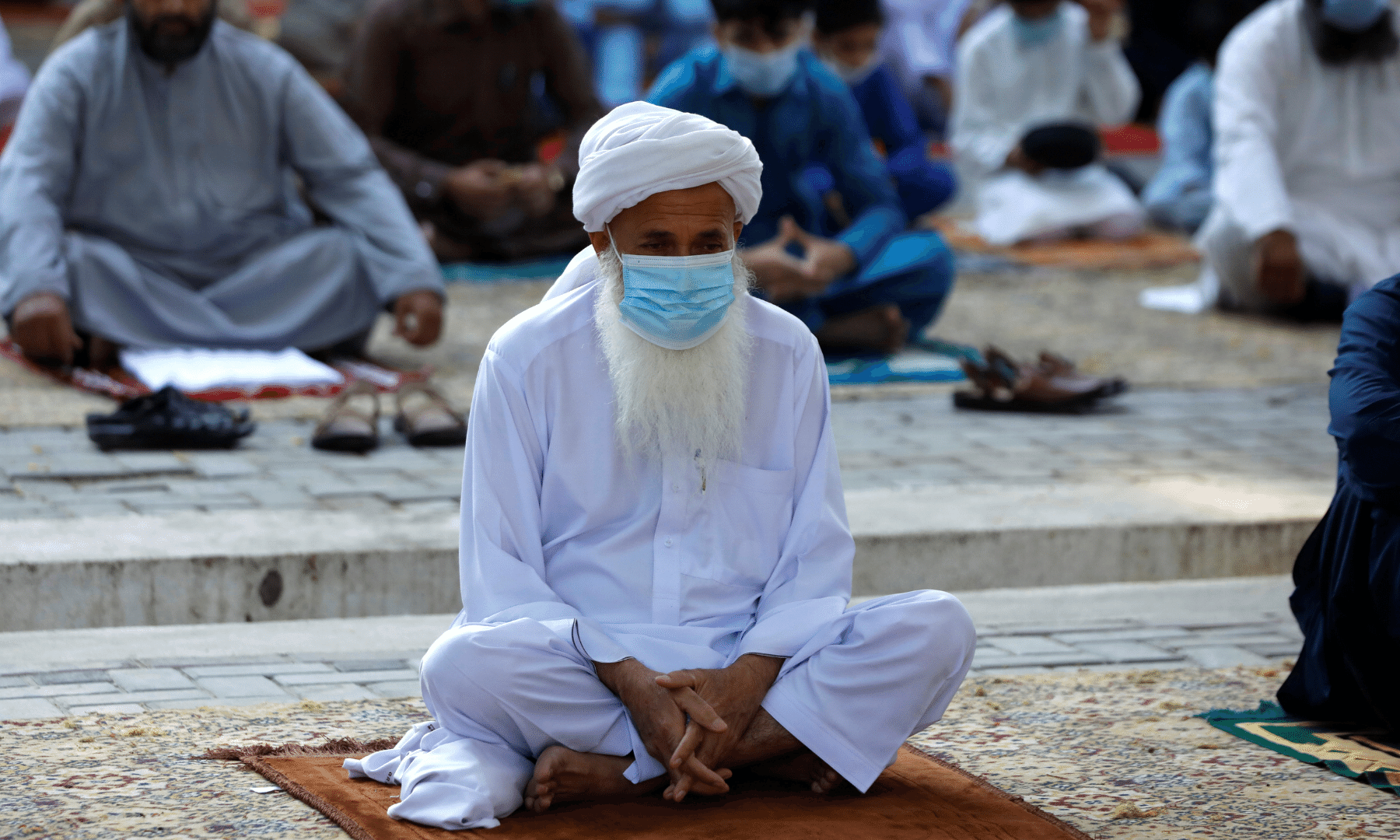 A man wears a protective mask maintaining social distance with others as they gather to for Eidul Fitr prayers in Peshawar on Thursday. — Reuters