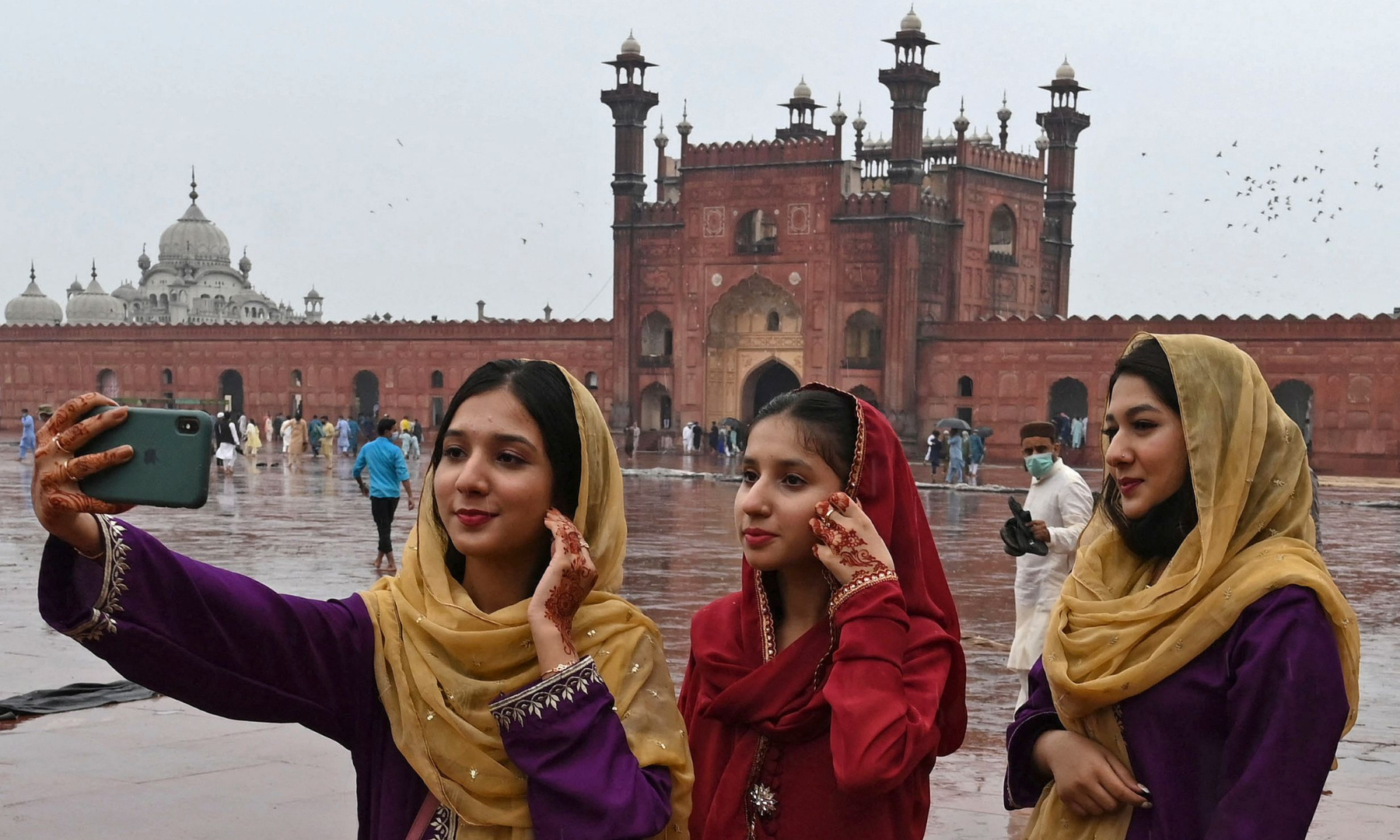 Muslim devotees takes a selfie using their mobile phones after offering special prayers on Eidul Fitr at the historic Badshahi Mosque in Lahore. — AFP
