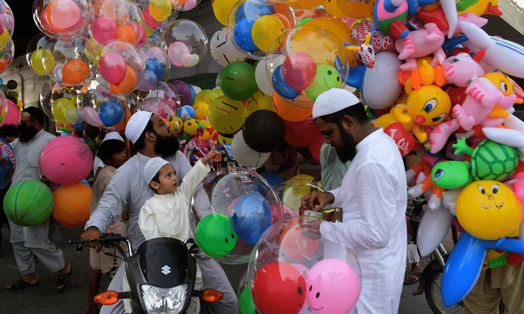 A child accompanying his parents buys balloons on the occasion of Eidul Fitr in Karachi. — AFP