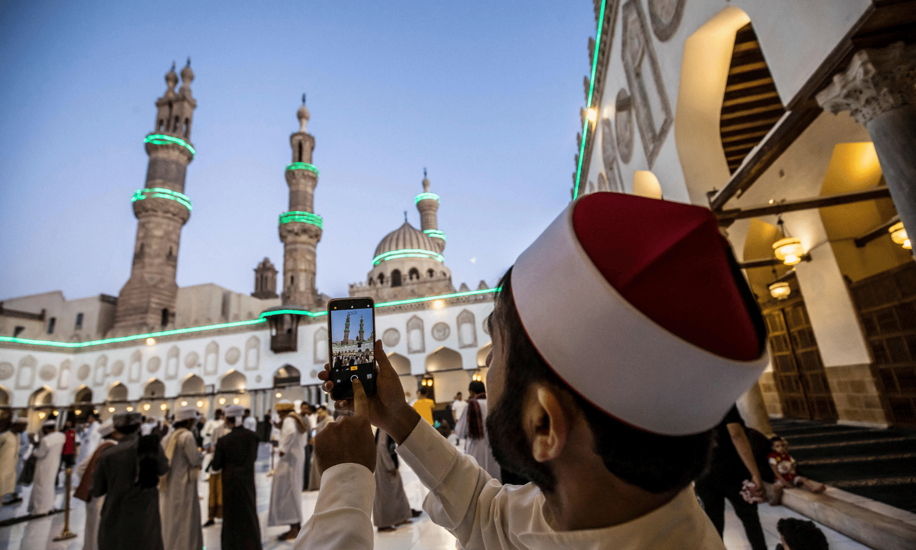 A Muslim worshipper takes pictures during Eidul Fitr prayers at al-Azhar mosque in the Egyptian capital Cairo. — AFP
