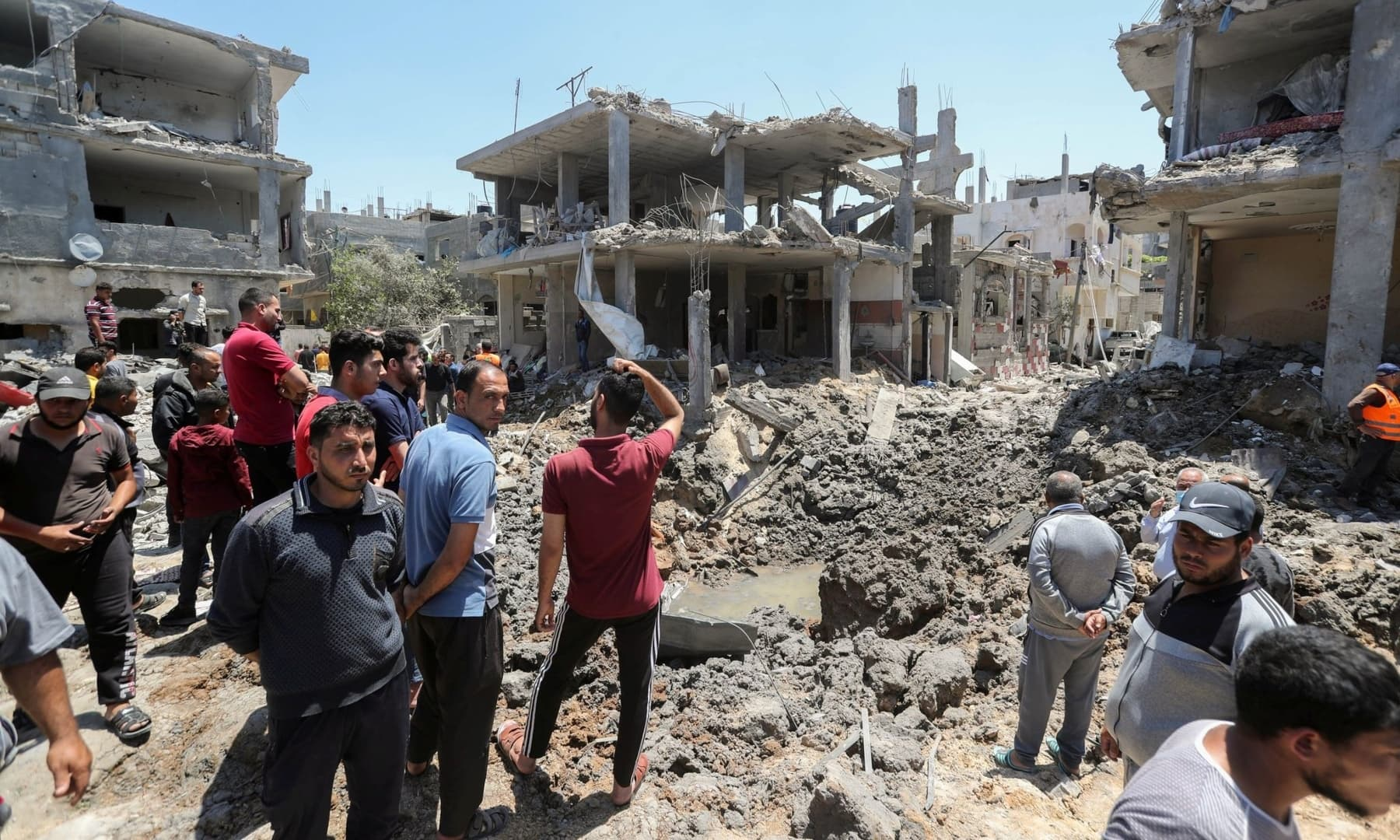 Palestinians gather at the site of destroyed houses in the aftermath of Israeli air and artillery strikes as cross-border attacks by the Israeli military continue, in the northern Gaza Strip, May 14, 2021. — Reuters