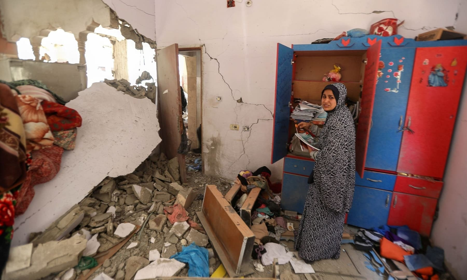 A Palestinian woman reacts as she collects her belongings inside her heavily damaged house in the aftermath of Israeli air and artillery strikes as cross-border attacks by the Israeli military continue, in the northern Gaza Strip, May 14, 2021. — Reuters