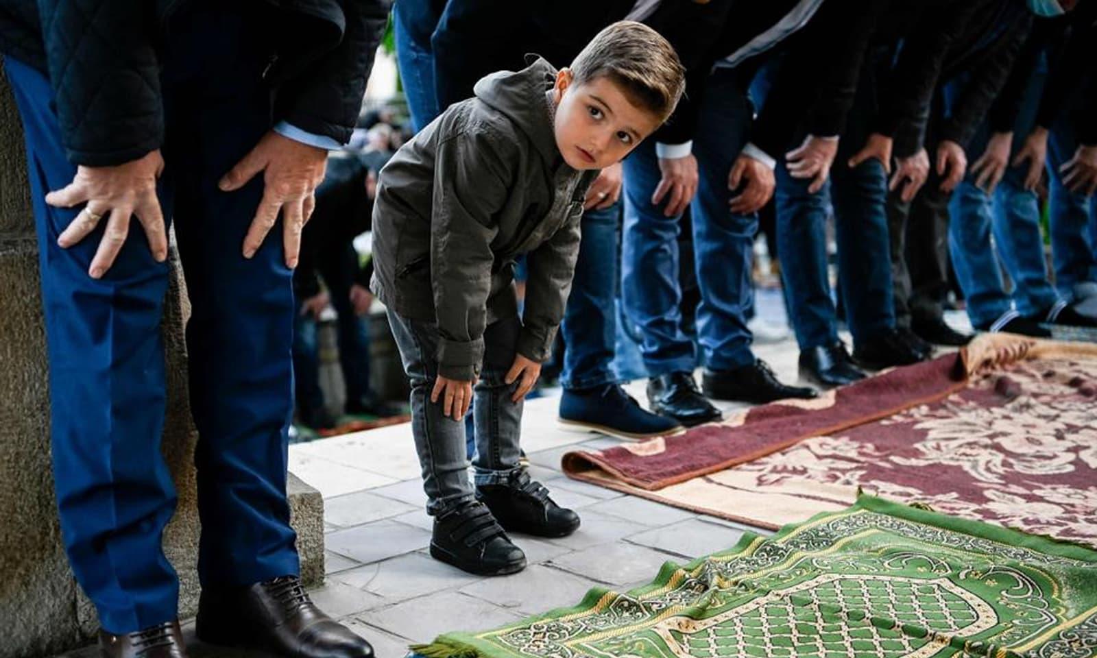 کوسوو میں بڑوں کے ساتھ بچے بھی نمازِ عید کی ادائیگی میں مصروف نظر آئے —فوٹو: اے ایف پی