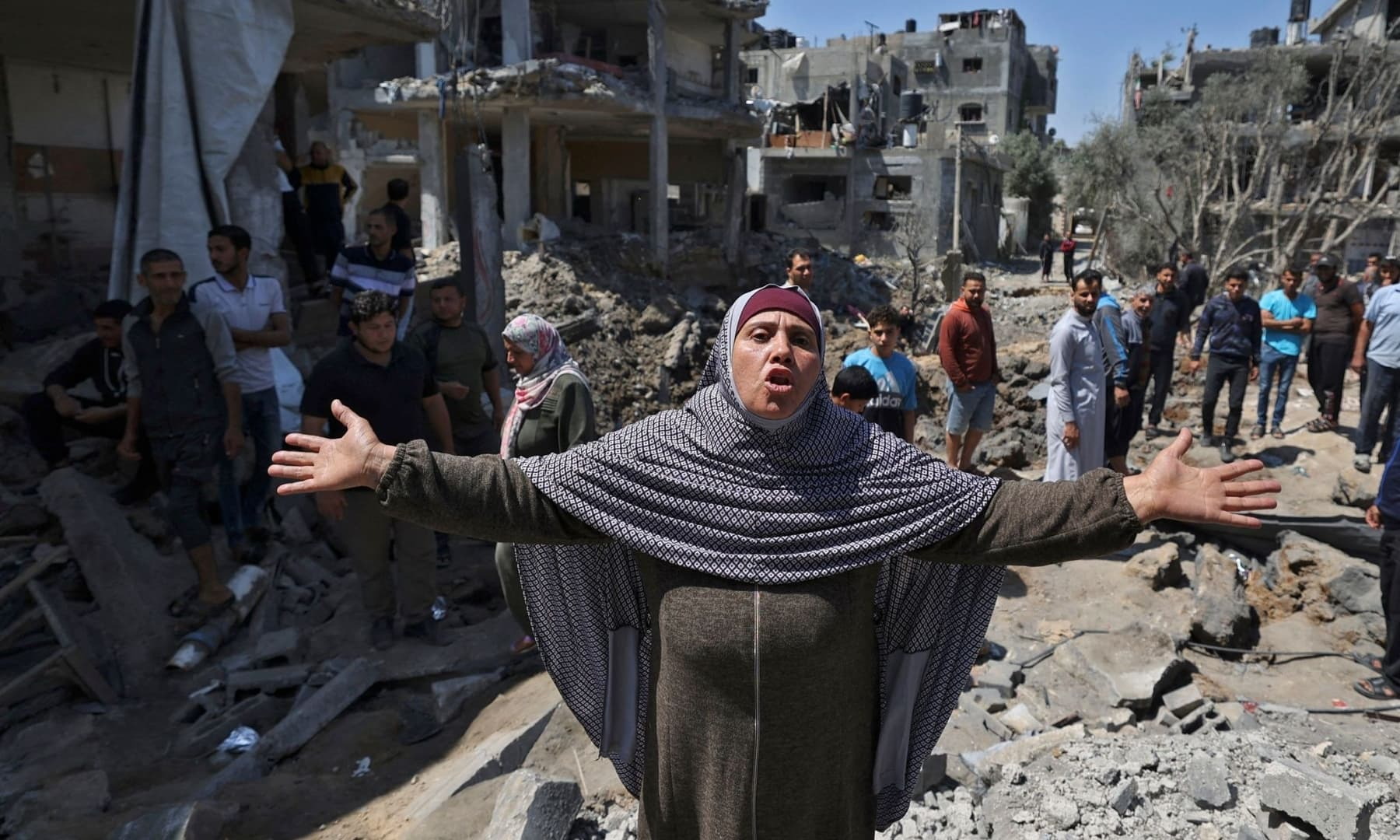 A Palestinian woman reacts as people assess the damage caused by Israeli air strikes, in Beit Hanun in the northern Gaza Strip, May 14, 2021. — AFP
