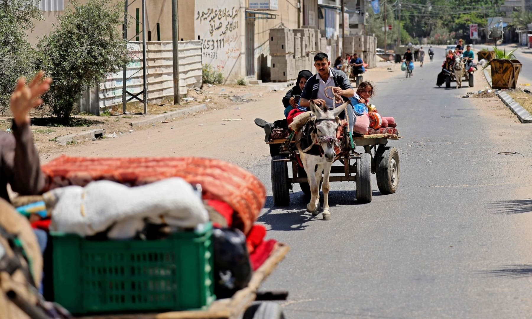 Members of a Palestinian family atop a carriage pulled by a donkey in Beit Lahya in the northern Gaza Strip, flee Israeli air and artillery strikes, to a safer location, May 14, 2021. — AFP