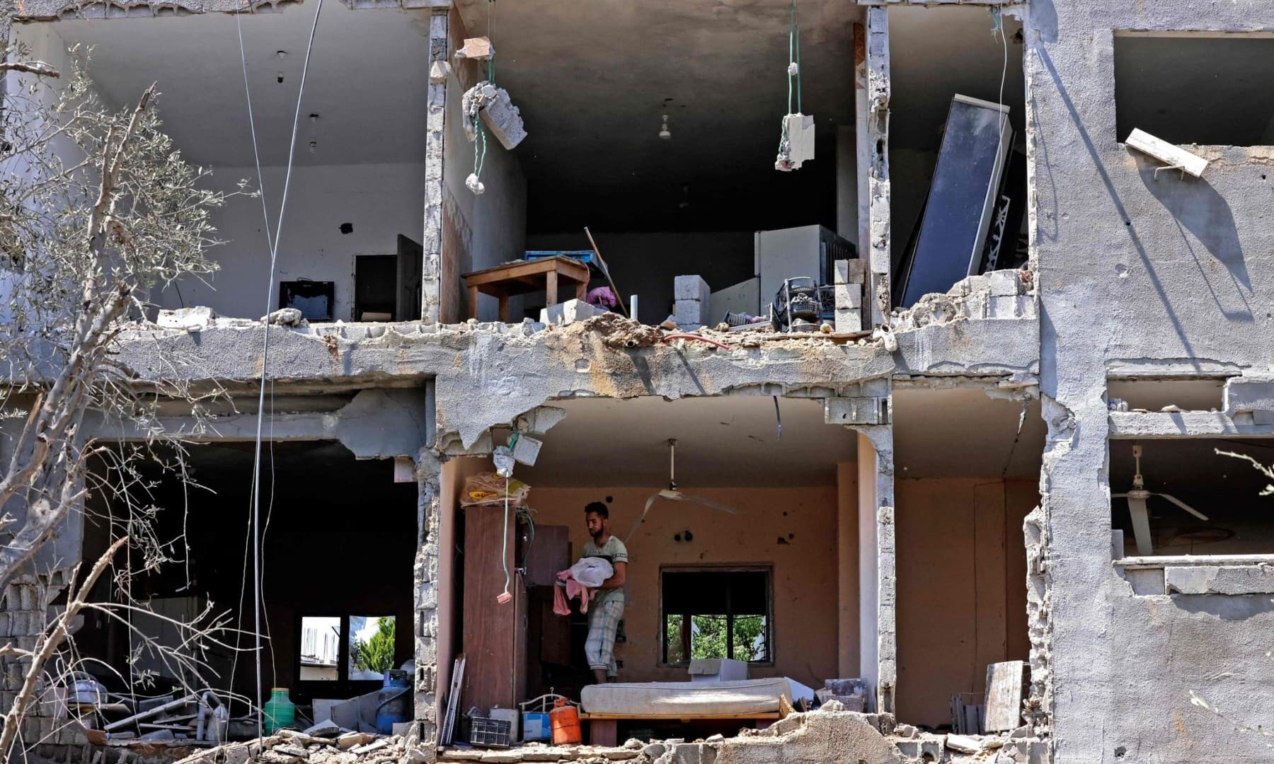 Palestinians assess the damage in a building caused by Israeli air strikes, in Beit Hanun in the northern Gaza Strip, May 14, 2021. — AFP