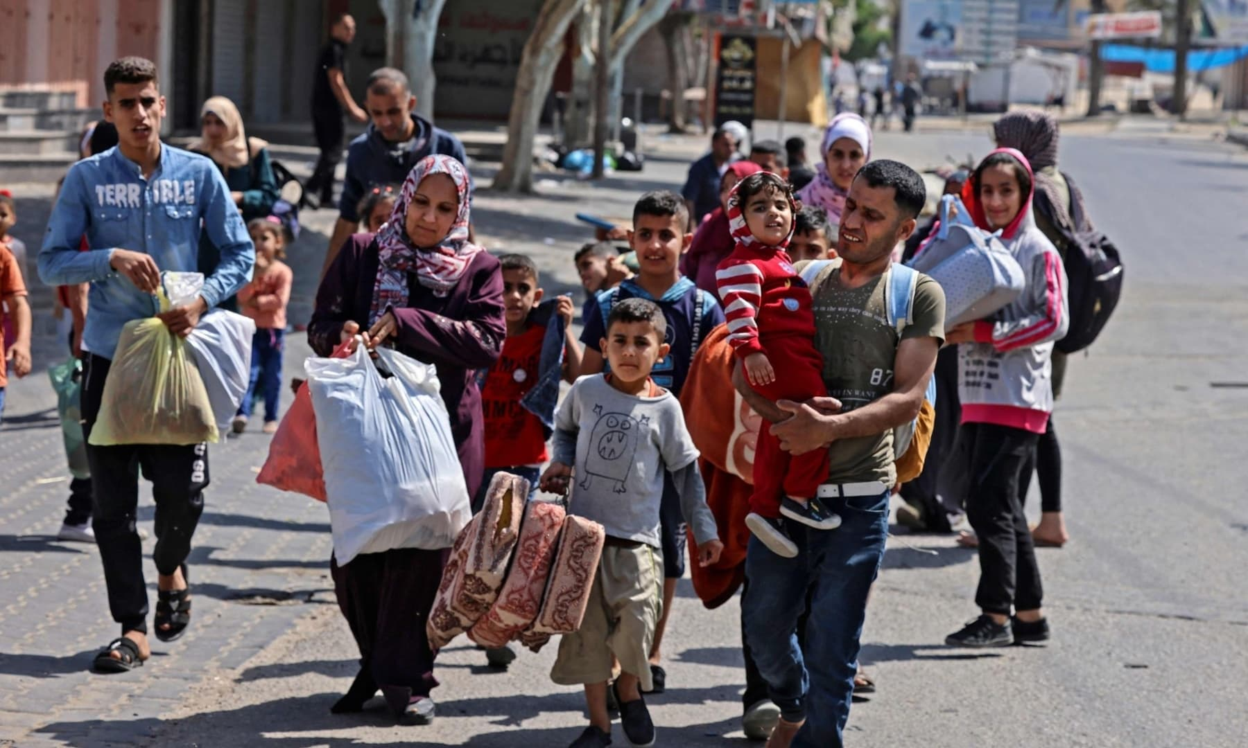 Palestinians carry some of their belongings in Beit Hanun in the northern Gaza Strip, as they flee Israeli air and artillery strikes, to a safer location, May 14, 2021. — AFP