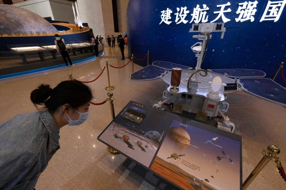 A visitor to an exhibition on China's space program looks at a life size model of the Chinese Mars rover Zhurong at the National Museum in Beijing on May 6. — AP