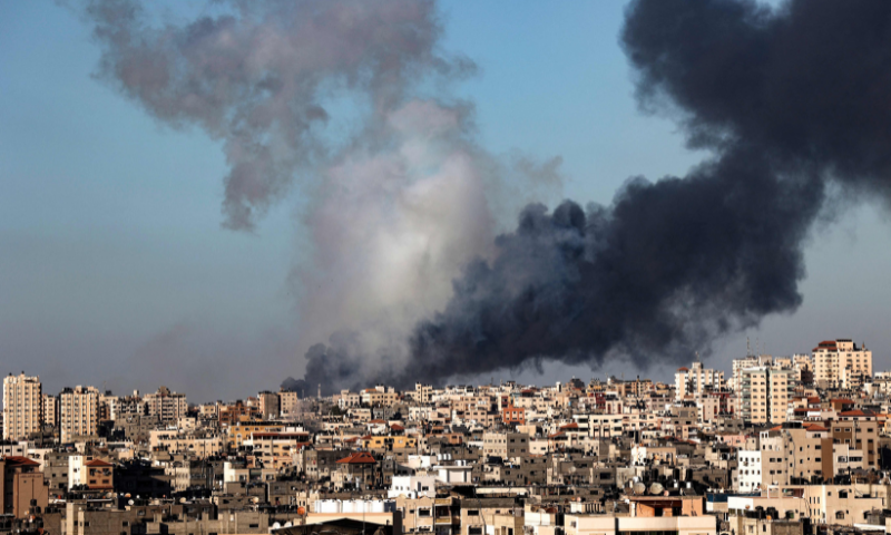 Plumes of smoke rise above buildings hit by Israeli airstrikes in Gaza City on Saturday. — AFP