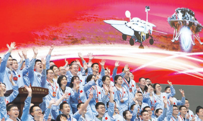 This photo released by the Xinhua News Agency shows scientists and technicians at the Beijing Aerospace Control Centre applauding the successful landing of China's spacecraft on the surface of Mars on Saturday.—AP