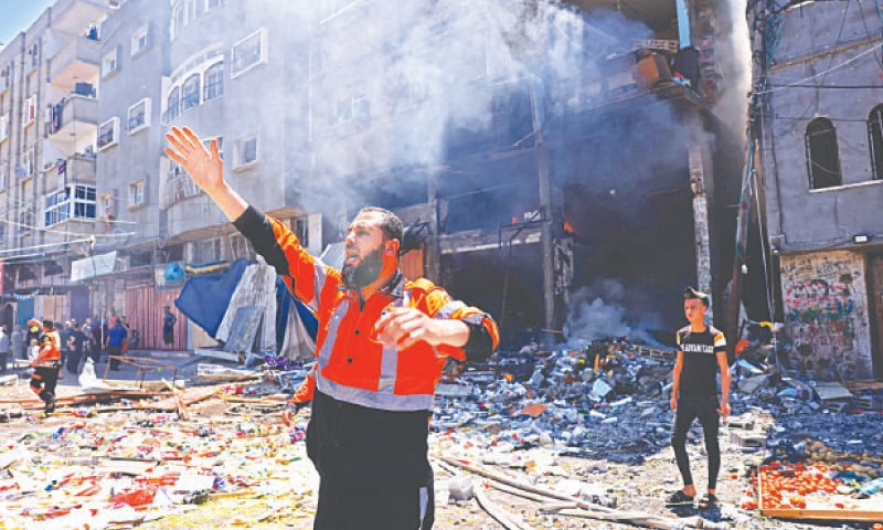 (Clockwise): A Palestinian firefighter shouts for help following an Israeli strike on Rafah town in the southern Gaza Strip on Saturday. Israeli forces try to detain a Palestinian woman in the east Jerusalem area of Sheikh Jarrah, where looming evictions of Palestinian families have fuelled anger, on May 15, the day on which Palestinians mark the 73rd anniversary of the Nakba, the 'catastrophe' of Israel's creation in 1948. A ball of fire erupts from the Jala Tower as it is destroyed in an Israeli air strike in Gaza city. People hold a demonstration in London in support of the Palestinian caus