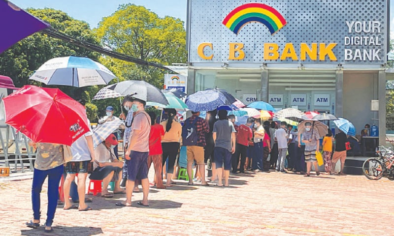 People line up outside a bank to withdraw cash in Yangon on Friday.—Reuters