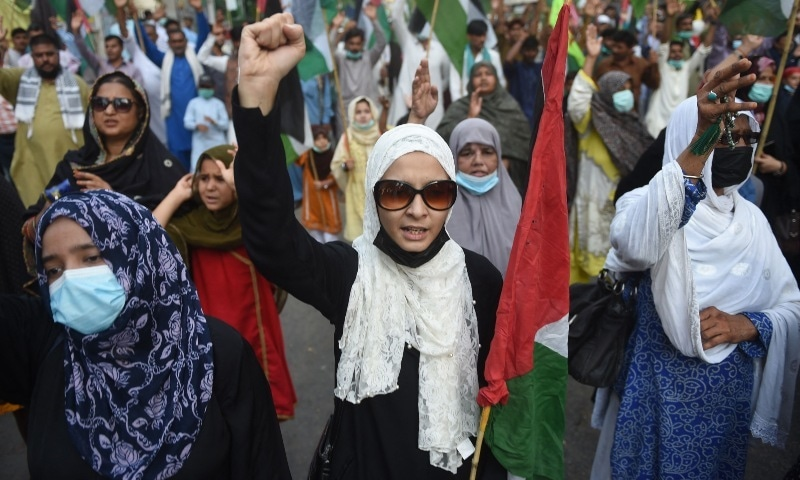 Protesters carrying Palestinian flags shout slogans during a protest against Israel's air strikes launched on the Gaza Strip, in Karachi on May 15, Saturday. — AFP
