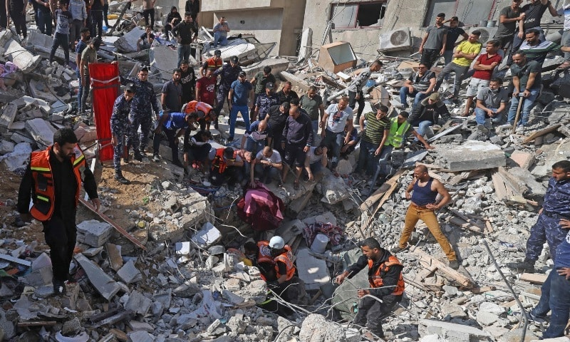 Palestinian paramedics search for survivors under the rubble of a destroyed building in Gaza City on May 16, 2021, following massive Israeli bombardment of the Hamas-controlled enclave. — AFP