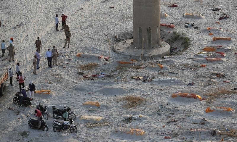 Policemen stand next to the bodies buried in shallow graves on the banks of Ganges river in Prayagraj, India, May 15. — AP