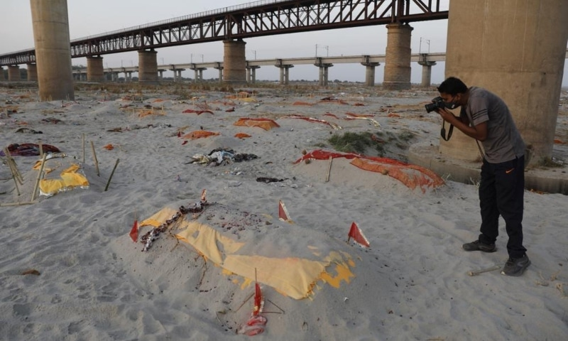 Bodies of suspected Covid-19 victims are seen in shallow graves buried in the sand near a cremation ground on the banks of Ganges River in Prayagraj, India, May 15. — AP