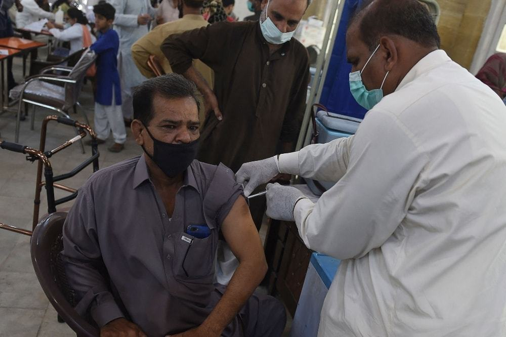 A health worker inoculates a man with a dose of AstraZeneca-Oxford's Covid-19 vaccine at a vaccination centre in Karachi on May 10. — AFP