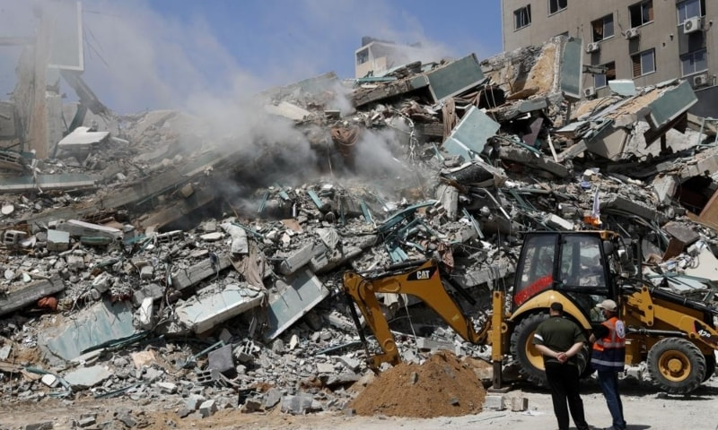 Workers clear the rubble of a building that was destroyed by an Israeli airstrike on Saturday, that housed The Associated Press, broadcaster Al-Jazeera and other media outlets, in Gaza City, May 16. — AP