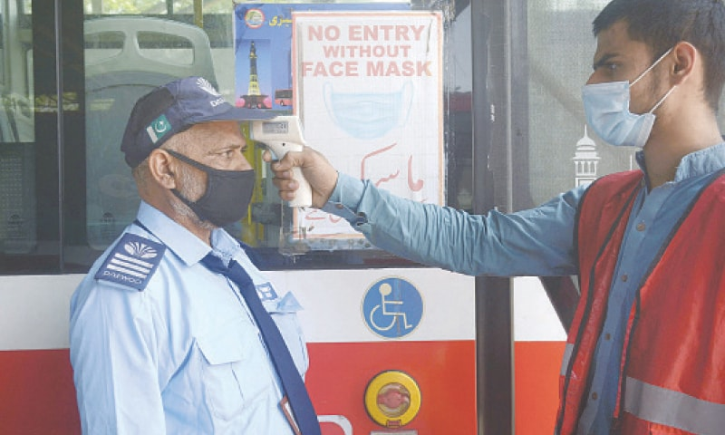 LAHORE: A metro bus ready to depart its station after the ban on transport was lifted on Sunday. [Right] A worker checking body temperature of a metro bus driver.—Online