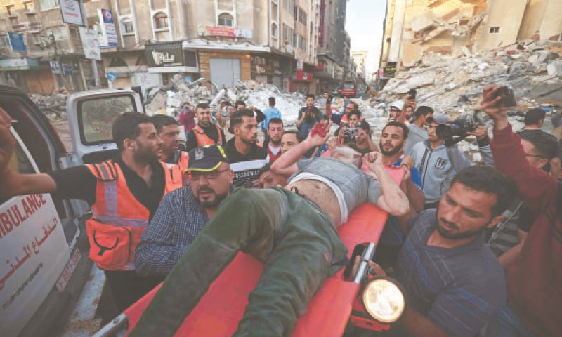 Palestinians carry one of the survivors from under the rubble of a building, after it was struck by Israeli strikes, in Gaza City.—AFP