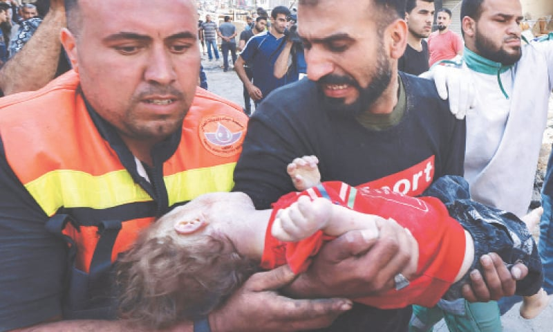 Palestinians recover the body of a child from the rubble of the destroyed building in Rimal. — AFP