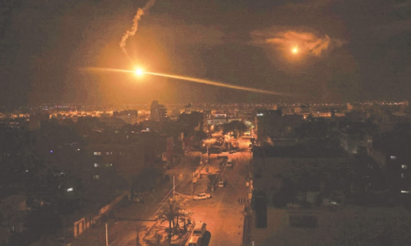 A flare fired by Israeli forces lights up the sky above the town of Rafah. — AFP
