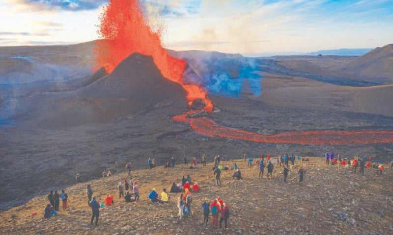 PEOPLE watch as lava flows from the Fagradalsfjall volcano, on the Reykjanes peninsula in south-western Iceland.—AP