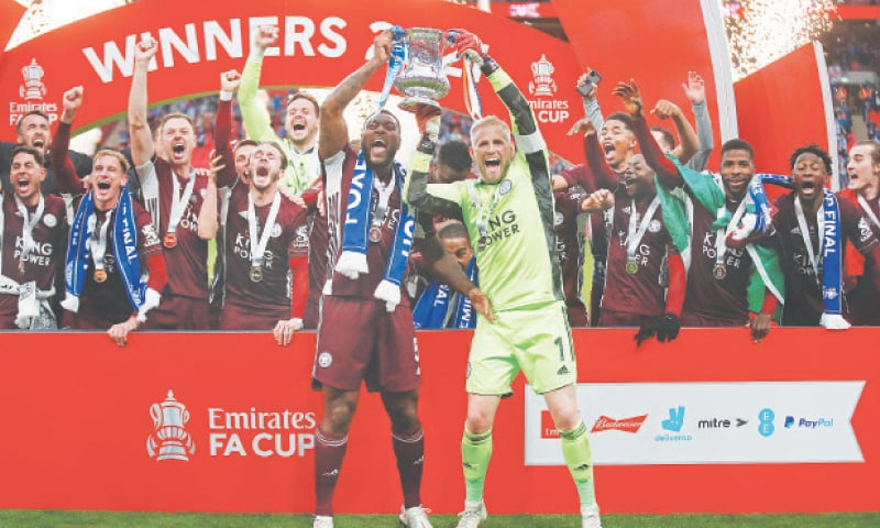 LONDON: Leicester City captain Wes Morgan and goalkeeper Kasper Schmeichel lift the trophy as their team-mates celebrate after winning the FA Cup final against Chelsea at Wembley.—Reuters