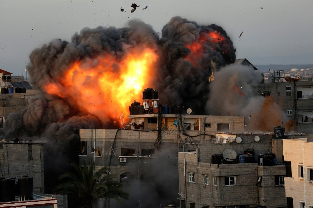 A ball of fire erupts from a building in Gaza City's Rimal residential district on May 16 during massive Israeli bombardment on the Hamas-controlled enclave. — AFP