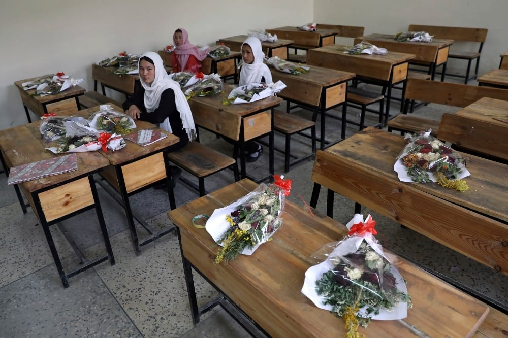 Schoolgirls sit inside a classroom with bouquets of flowers on empty desks as a tribute to those killed in the brutal May 8 bombing of the Syed Al-Shahda girls school, in Kabul. - AP