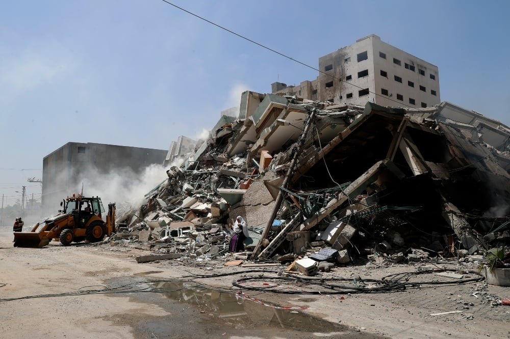 Workers clear the rubble of a building that was destroyed by an Israeli airstrike, that housed The Associated Press, broadcaster Al-Jazeera and other media outlets, in Gaza City on May 16. — AP