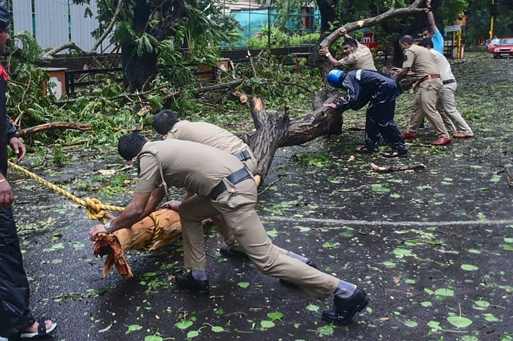 Police personnel clear fallen trees from a road following severe cyclonic storm 'Tauktae', at Panjim in Goa on May 16. — AFP