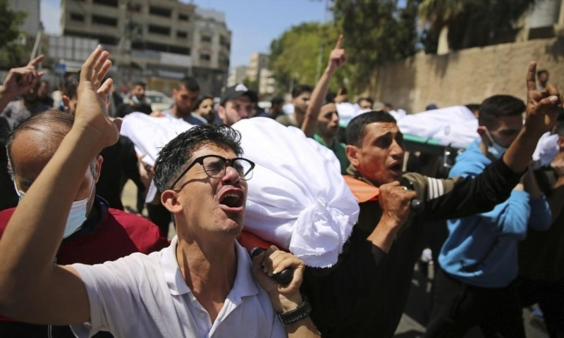 Mourners carry the the bodies of Palestinians who were killed in overnight Israeli airstrikes that hit their homes, during their funeral in Gaza City, May 16. — AP