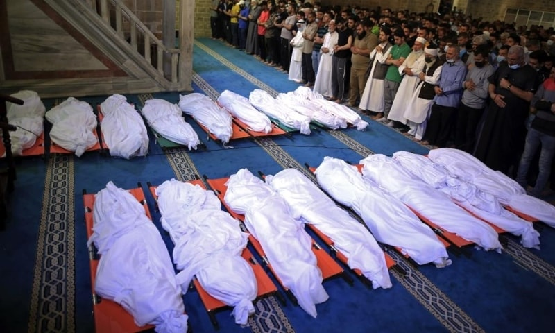 Mourners pray over the bodies of 17 Palestinians who were killed in overnight Israeli airstrikes in Gaza City, May 16. — AP