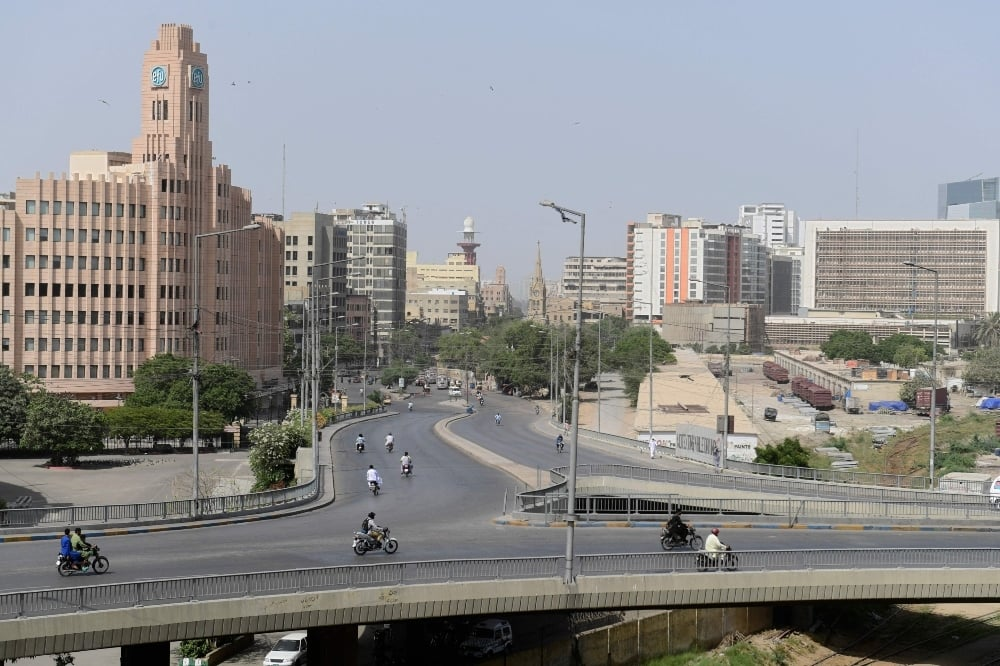 Commuters make their way through a partially deserted bridge during a nine-day nationwide lockdown imposed to curb the spread of the Covid-19 coronavirus in Karachi on May 16. - AFP