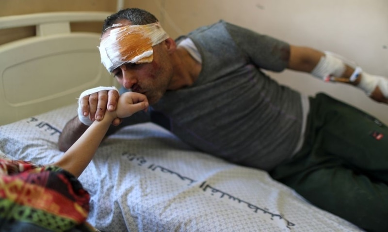 Riyad Eshkuntana kisses his daughter Suzy's hand as they are treated at a hospital after being pulled from the rubble of a building amidst Israeli air strikes, in Gaza City, May 16. — Reuters