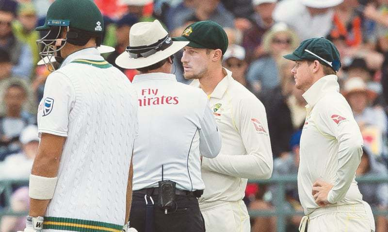 In this file photo, Cameron Bancroft of Australia (second R) is questioned by the umpire regarding ball tampering as captain Steve Smith looks on. - AP//File