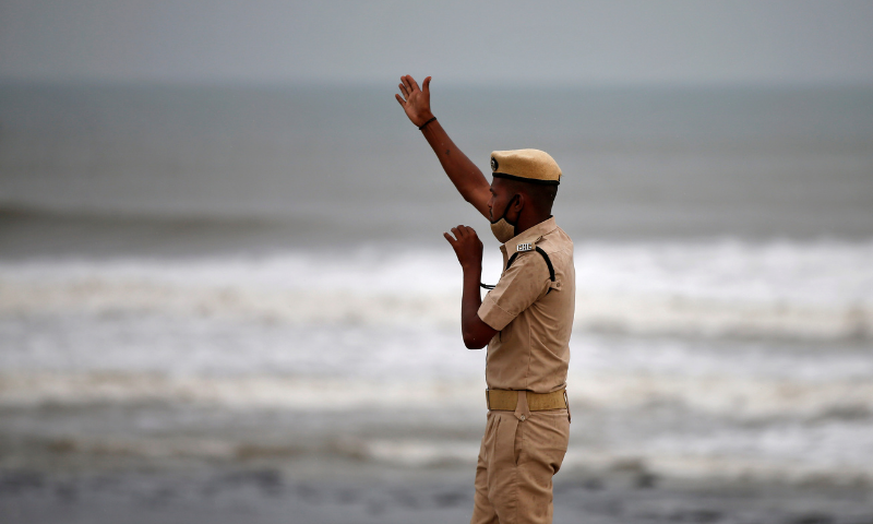 A policeman directs people to leave as waves approach the shore ahead of Cyclone Tauktae in Veraval in the western state of Gujarat, India, on Monday. — Reuters