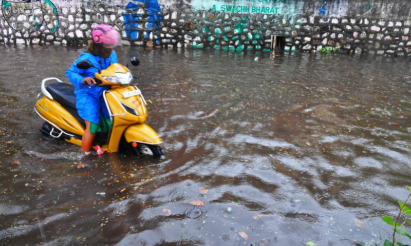 A woman rides a scooter through a waterlogged street following heavy rains from Cyclone Tauktae in Mumbai on Monday. — AFP