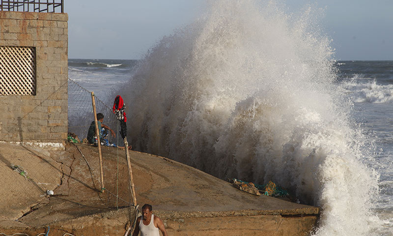In this file photo, a boy looks as a high wave smashes into the shore in Karachi. — AP/File